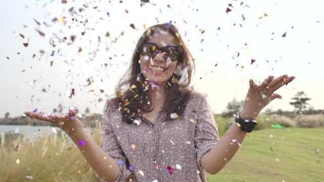 vidéos et rushes de femme asiatique jetant des confettis au ralenti - jetée