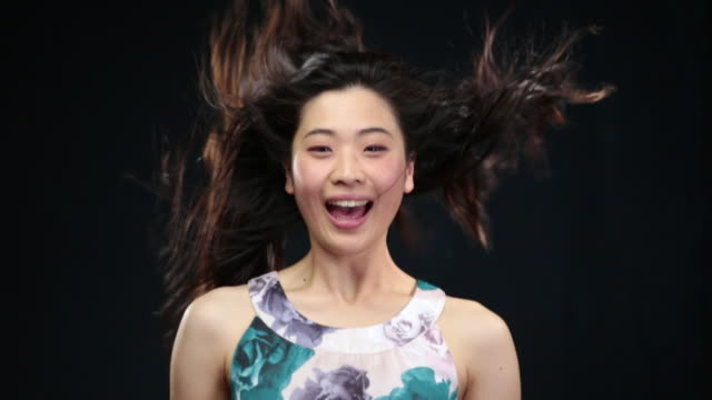 ms slo mo asian woman throwing head up in air and turning head from side to side, hair moving in wind / london, greater london, united kingdom - rufsig bildbanksvideor och videomaterial från bakom kulisserna