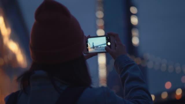 Turista de mulher asiática usando smartphone tomar um panorama da fotografia do rio à noite.