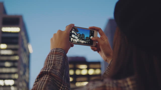 asian woman tourist using smartphone take a photo panorama of tokyo city at night. - photo messaging stock videos & royalty-free footage