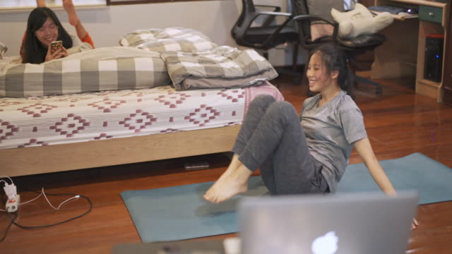 asian woman training her abs at home on exercise mat - lying on front stock videos & royalty-free footage