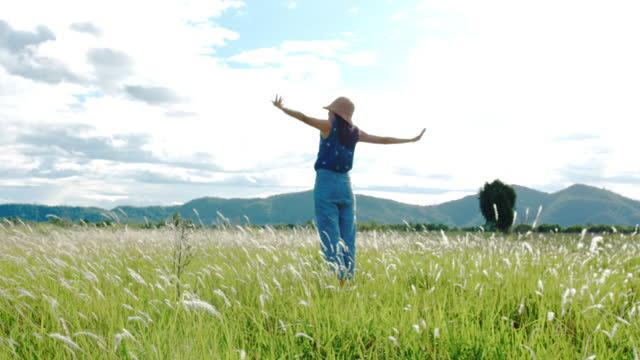 vidéos et rushes de voyage asiatique de femme au sentier de nature avec la vue scénique du domaine vert de pré avec le fond de ciel de montagne et bleu.4k ralenti. - aventure