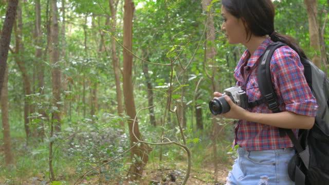 Aziatische vrouw reizen buiten levensstijl meenemen fotografische camera in bos