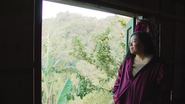 vídeos de stock, filmes e b-roll de mulher asiática viajante abrir janela de resort homestay em floresta tropical no topo do fundo da montanha. conceito de viagem na natureza.4k câmera lenta. - floresta pluvial