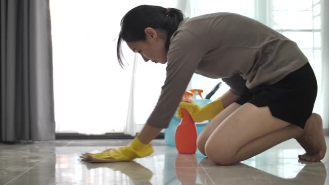 asian woman tries to remove a stain on the floor with spray cleaning product - domestic kitchen stock videos & royalty-free footage