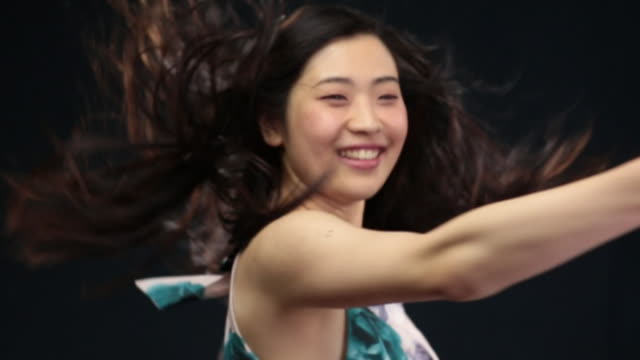 vídeos de stock, filmes e b-roll de ms slo mo asian woman turning around in circles, hair moving in wind / london, greater london, united kingdom - exposto pelo vento