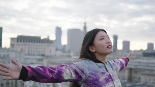 asian woman turning on roof with opened arms - vita cittadina video stock e b–roll