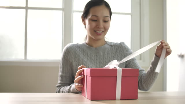 asian woman unleashes a white bow and opening gift box at home - embarrassment stock videos & royalty-free footage