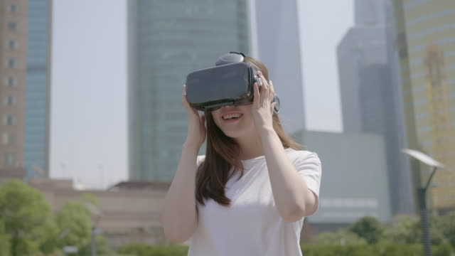 Asian woman use a Vr glasses in Urban setting