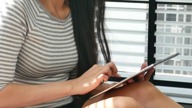 vídeos y material grabado en eventos de stock de mujer asiática utilizar la tableta para relajarse - píldoras