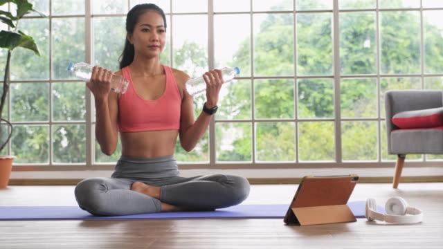 vídeos de stock e filmes b-roll de asian woman use water bottle as dumbbell weight training online course with tablet at home.wide shot - flexão de braço com peso