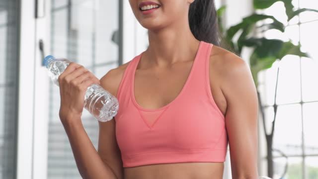 vídeos de stock e filmes b-roll de asian woman use water bottle as dumbbell weight training online course with tablet at home.close up shot - flexão de braço com peso
