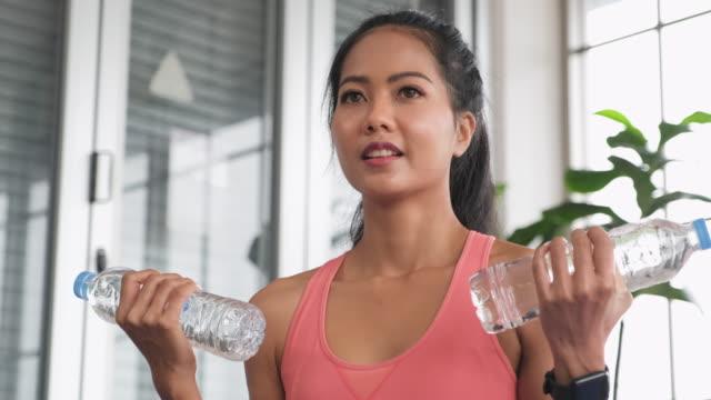 vídeos de stock e filmes b-roll de asian woman use water bottle as dumbbell weight training online course with tablet at home - flexão de braço com peso