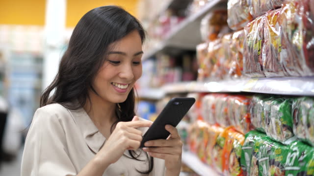 asian woman uses smart phone in supermarket - groceries stock videos & royalty-free footage