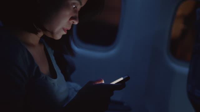 asiatische frau nutzt das telefon, an das fenster des flugzeugs sitzen - passagier stock-videos und b-roll-filmmaterial
