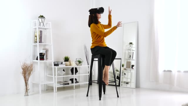 Asian Woman using 360 VR glasses of virtual reality in living room at home