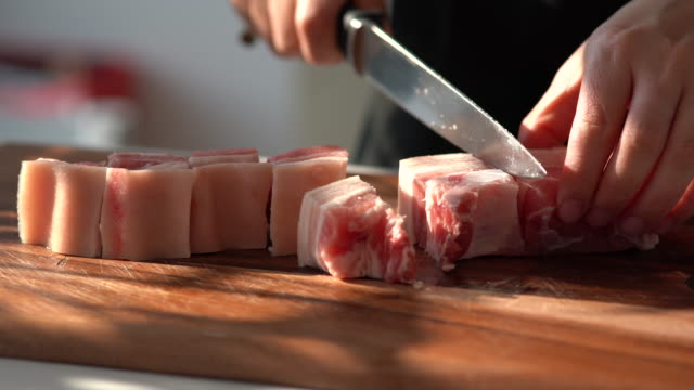 asian woman using a knife to cut pork into pieces - chopping board stock videos & royalty-free footage
