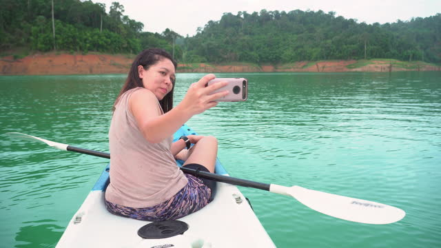 asian woman using a smartphone to take photos, selfies, taking relaxation among natural blue khao sok lake with outdoor activities, padding with kayak in summer holiday vacation. - natural black hair stock videos & royalty-free footage
