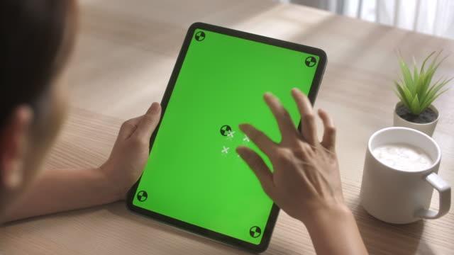 vídeos y material grabado en eventos de stock de mujer asiática usando en la tableta digital con pantalla verde - tecla de piano