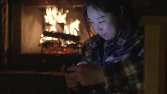 asian woman using cell phone by fireplace - chinaface stock videos & royalty-free footage