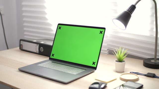 vidéos et rushes de femme asiatique utilisant l'écran de clé de chroma sur l'ordinateur portatif sur le bureau - modèle réduit