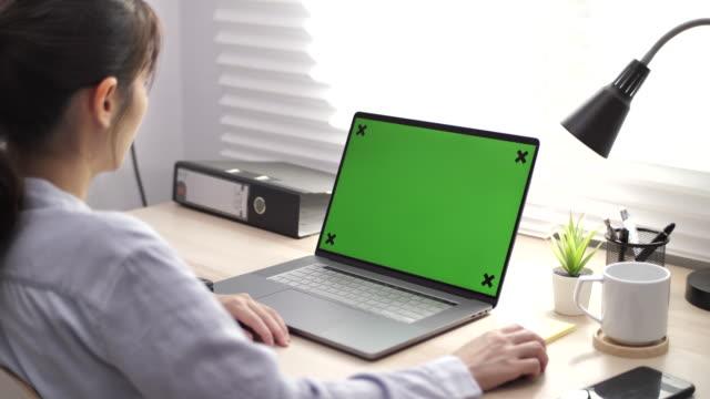 vídeos y material grabado en eventos de stock de mujer asiática usando la pantalla de la llave de croma en el ordenador portátil en el escritorio - exhibir