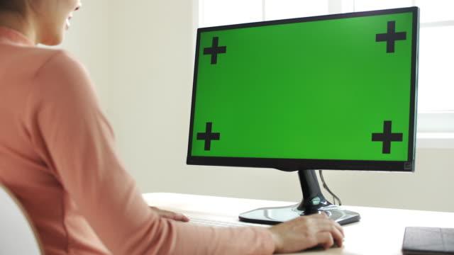 vídeos de stock, filmes e b-roll de mulher asiática usando computador com tela verde - monitor de computador
