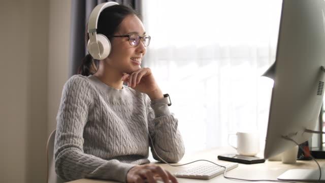vidéos et rushes de femme asiatique utilisant l'ordinateur avec le casque à la maison - online messaging