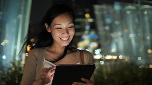 asian woman using digital tablet at night - window display stock videos & royalty-free footage