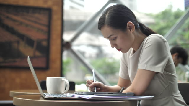 asian woman using digital tablet for her working in cafe, using digitized pen - coffee cup stock videos & royalty-free footage