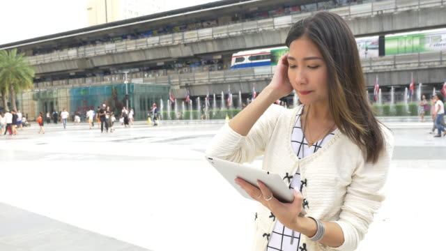 asian woman using digital tablet in city - transportation building type of building stock videos & royalty-free footage