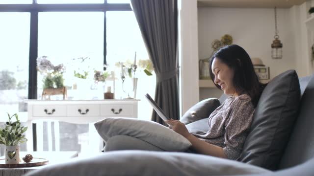 アジアの女性を使用してデジタル タブレットの自宅のリビング ルームでソファの上 - 居間点の映像素材/bロール
