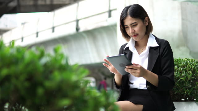 asian woman using digital tablet outside - business casual stock videos & royalty-free footage