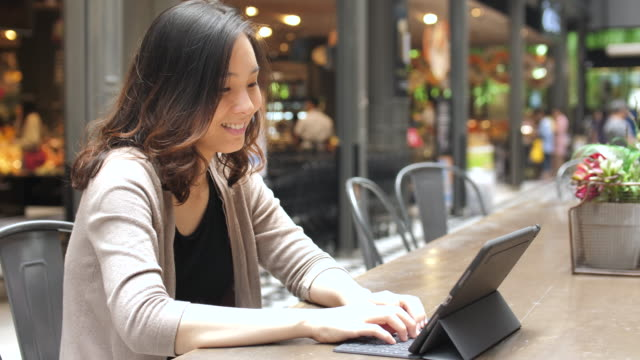 Asian Woman using Digital tablet outside