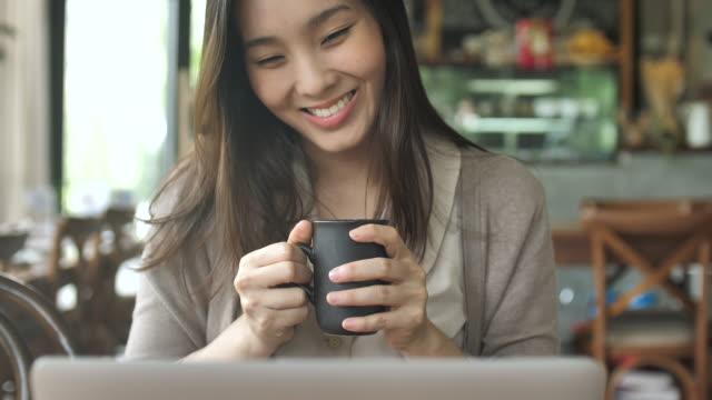 アジアの女性がコーヒーを飲むとラップトップを使用して - カップ点の映像素材/bロール