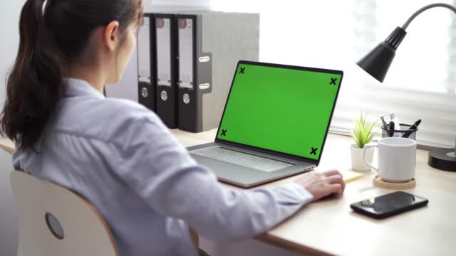 vídeos de stock, filmes e b-roll de mulher asiática usando tela verde laptop no escritório - modelo web