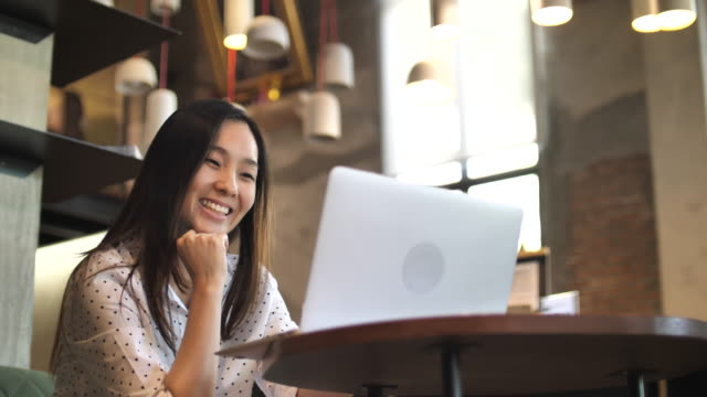 asian woman using laptop in cafe, slow motion - laptop video stock e b–roll