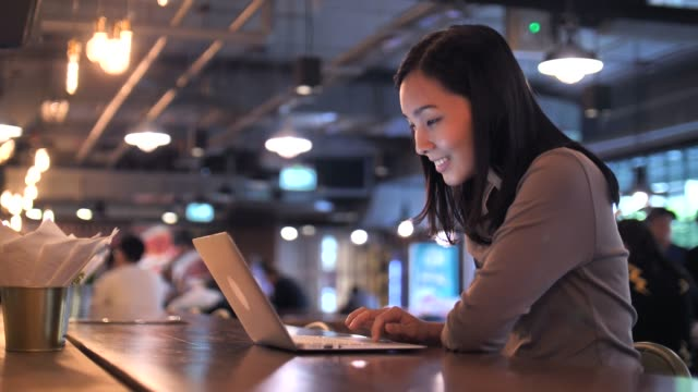 asian woman using laptop in cafe - freelance work stock videos & royalty-free footage