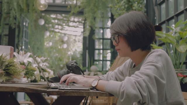 vídeos de stock e filmes b-roll de asian woman using laptop in the restaurant. - trabalhadora de colarinho branco
