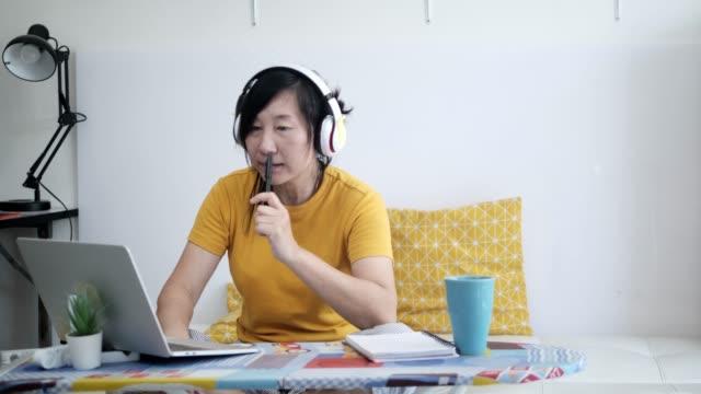 asiatisk kvinna som använder bärbar dator på strykbräda eller arbetar hemma under covid-19. - endast en medelålders kvinna bildbanksvideor och videomaterial från bakom kulisserna