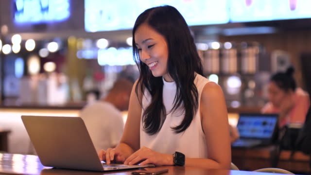 asian woman using laptop working freelance at cafe - using laptop stock videos & royalty-free footage