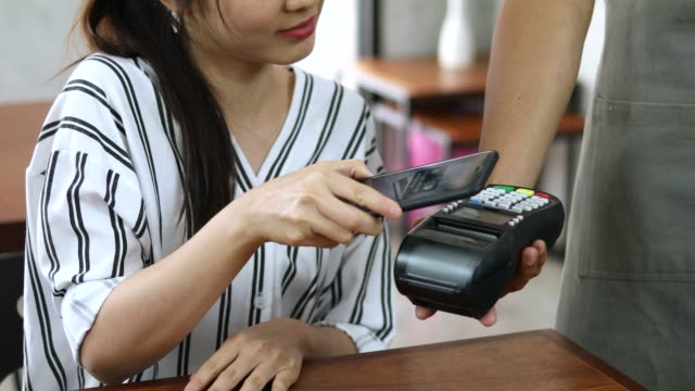 asian woman using mobile payment in cafe - radio frequency identification stock videos & royalty-free footage