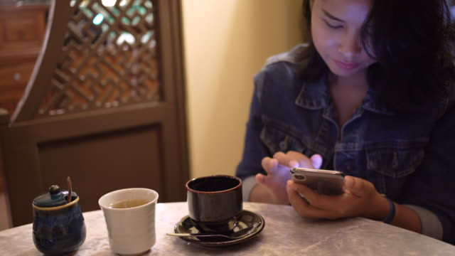 asian woman using mobile phone and drink coffee in the cafe - coffee drink stock videos & royalty-free footage