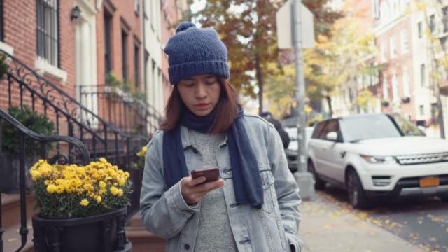 stockvideo's en b-roll-footage met aziatische vrouw met behulp van mobiele telefoon tijdens lopen op straat - alleen één mid volwassen vrouw