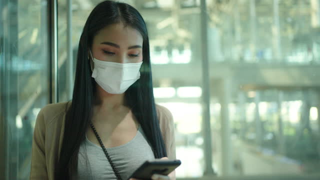 asiatische frau mit handy in flughafen, tragen medizinische maske. - fahrstuhlperspektive stock-videos und b-roll-filmmaterial