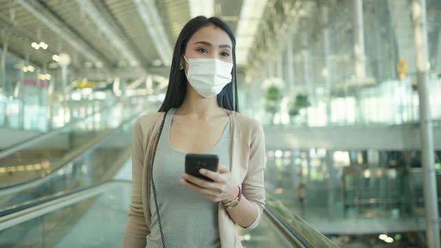 vidéos et rushes de femme asiatique utilisant le téléphone portable à l'aéroport, portent le masque médical. - difficultés dans le couple
