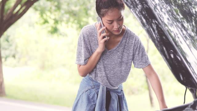 Asiatisk kvinna med mobiltelefon medan du tittar och stressad kvinna efter brutit ner bilen på gatan