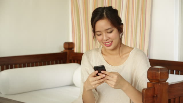 MS Asian woman using mobile phone whilst sitting down