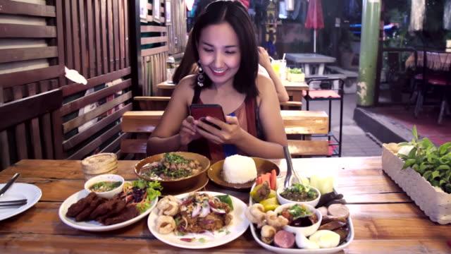 vidéos et rushes de femme asiatique utilisant le téléphone intelligent mobile prenant le groupe de photo des nourritures thaïlandaises. - blog