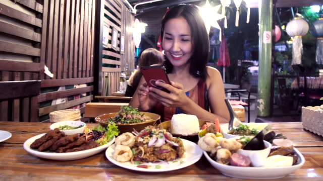 asian woman using mobile smart phone taking photo group of thai foods. - thai culture stock videos & royalty-free footage